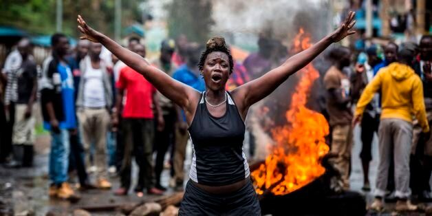 An opposition supporter reacts under the heavy rain in front of a burning barricade in Mathare district,...