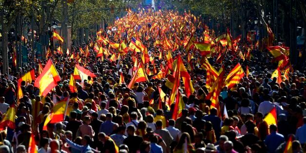 People wave Spanish and Catalan Senyera flags during a pro-unity demonstration in Barcelona on October...