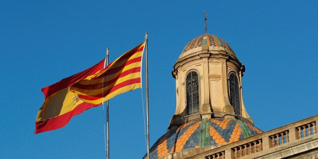 Spanish (L) and Catalan flags flutters atop the Generalitat Palace, the Catalan regional government headquarter...