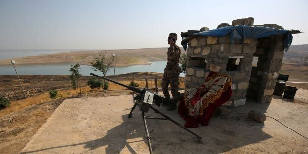 Iraqi forces stand guard at the Mosul Dam in the northern Iraqi city of Mosul on October 24, 2017. /...