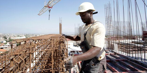 Kamara, 29, a migrant from Guinea, works at the construction site of a building in Algiers, Algeria June...