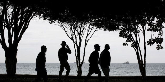 African migrants walk in front the Mediterranean Sea in Spain's north African enclave of Ceuta, Spain,...