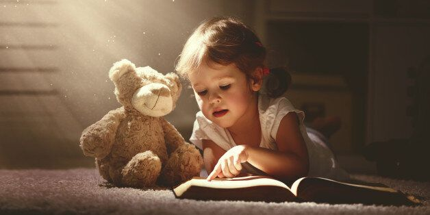 child little girl reading a magic book in the dark home with a toy teddy