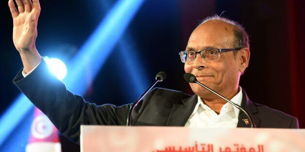 Former Tunisian president Moncef Marzouki waves to his supporters during a rally to launch his new political...