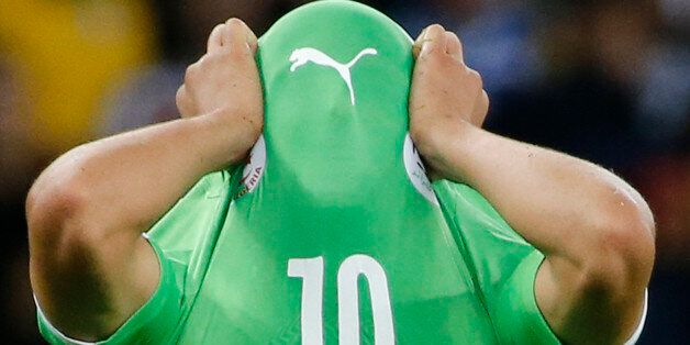 Algeria's Sofiane Feghouli covers his face with his jersey as he reacts to his team's loss at the end...