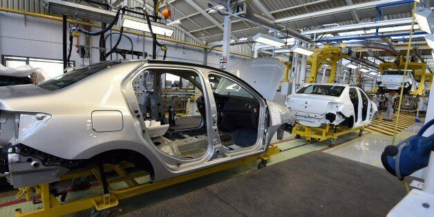 Employees of the French car maker Renault group work on a new production line during its inauguration...
