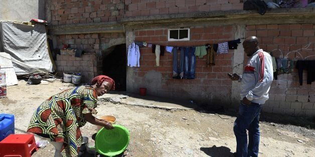 A Sub-Saharan woman does some washing-up at the bottom of a makeshift building, where she lives with...