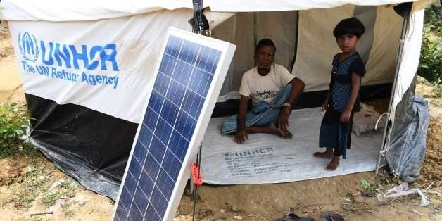 This photo taken on October 7, 2017 shows Rohingya refugees waiting for a solar lantern to charge at...