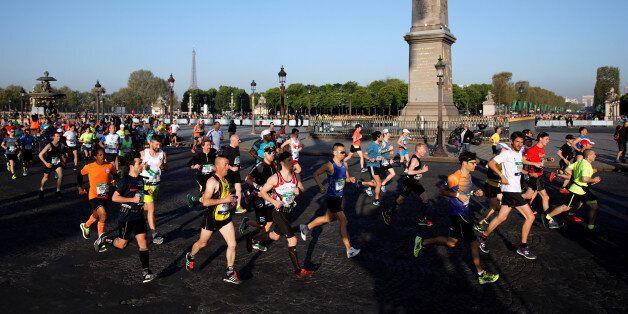 Competitors run down the Champs Elysees below the Arc de Triomphe at the start of the 41st Paris Marathon...