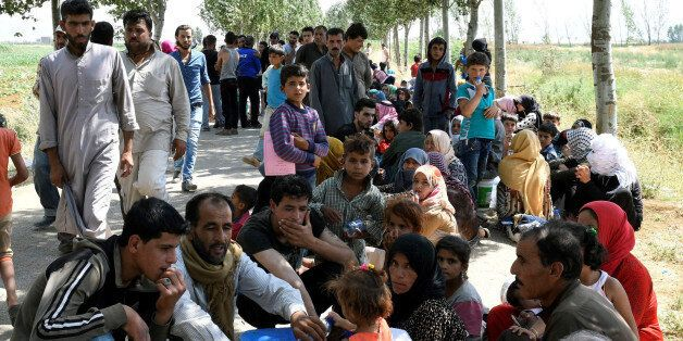 Syrian refugees gather outside their camp after a fire tore through it, near the town of Qab Elias, in...