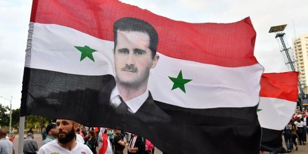 Syrian migirants carry their national flags and pictures of Syrian President Bashar al-Assad jubilate...