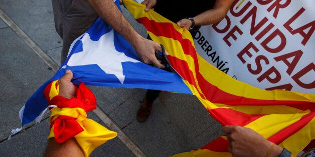 MADRID, SPAIN - OCTOBER 07: Demonstrators cut off the star from a Catalan Pro-Independence flag known...