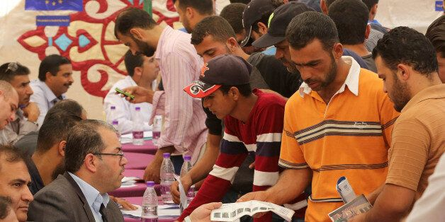 Syrian refugees queue to register their names at the Zaatari office for employment on October 4, 2017...