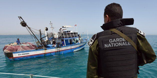 TO GO WITH AFP STORY BY KAOUTHER LARBI A member of the Tunisia's national guard stops a fishing boat...