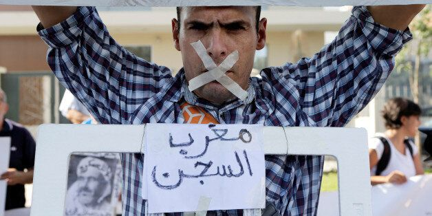 A relative of the leaders of Morocco's Hirak protest movement displays a placard that