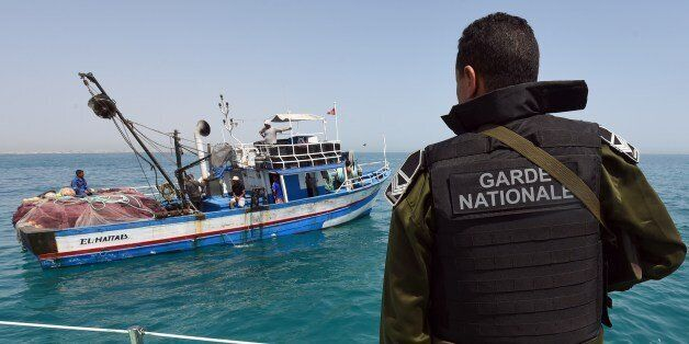 A member of the Tunisia's national guard stops a fishing boat in the sea bordering Tunisia and Libya...