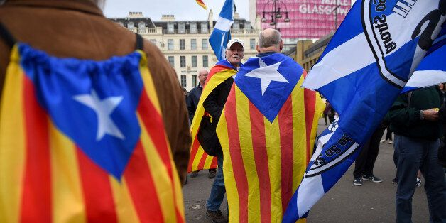 Demonstrators display the Catalan Flag, the Senyera (L) and the Flag of Scotland, the Saltire (R) painted...