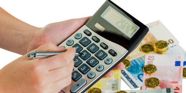 (GERMANY OUT) Hand mit Taschenrechner und Geldscheinen. Symbolfoto für Umsatz, Gewinn, Steuern und Kalkulation...