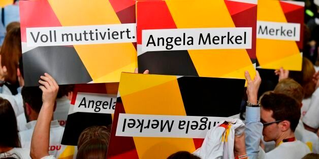 Supporters of the Christian Democratic Union (CDU) react with banners as exit poll results were broadcasted...