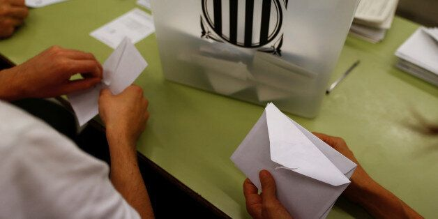 Poll workers count ballots after polls closed at a polling station for the banned independence referendum...