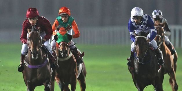 Female Qatari jockey Maryam Al-Subaiey (L) participates in a horse race at the Racing and Equestrian...
