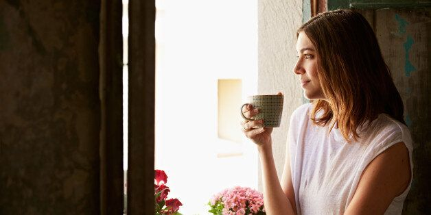 Shot of a young woman drinking a cup of coffee while looking out of a