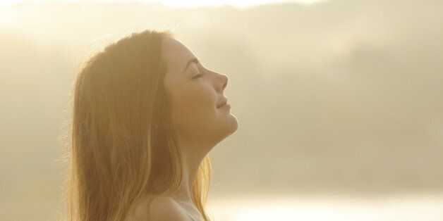 Backlight profile of a woman breathing deep fresh air in the morning sunrise isolated in white