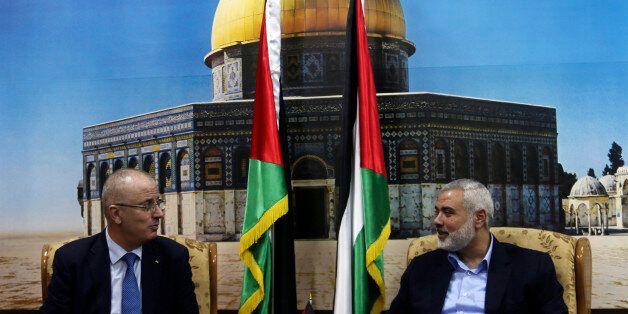 Senior Hamas leader Ismail Haniyeh (R) speaks with Palestinian Prime Minister Rami Hamdallah at Haniyeh's...