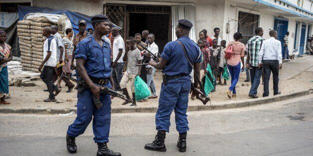 Burundian policemen investigate the scene of a grenade attack in central Bujumbura that left eight people...