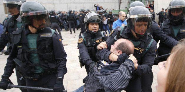 Spanish Guardia Civil guards drag a man outside a polling station in Sant Julia de Ramis, where Catalan...