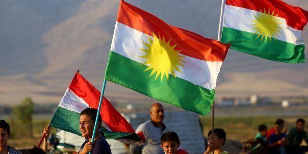 Syrian Kurds wave the Kurdish flag, in the northeastern Syrian city of Qamishli on September 27, 2017,...