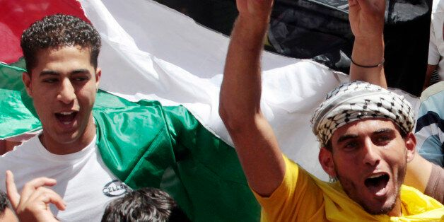 Fatah supporters take part in a rally celebrating the reconciliation agreement between rival Palestinian...