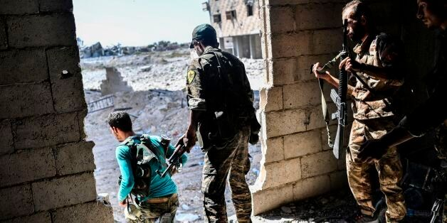 Members of the Syrian Democratic Forces hold a position as they advance to take the central hospital...