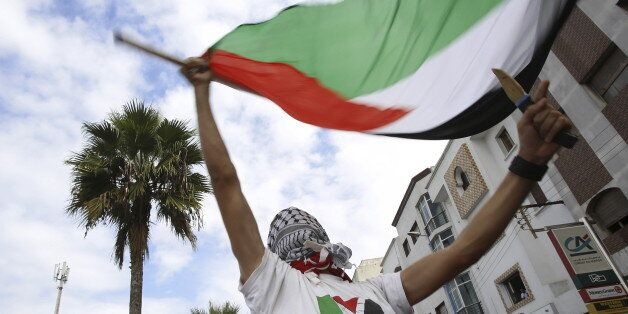 Pro-Palestinian protester holds Palestinian flag and dummy knife during a demonstration organized by...