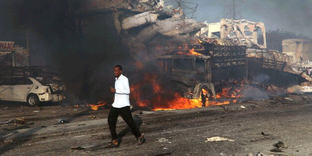 A man runs past the scene of an explosion in KM4 street in Hodan district of Mogadishu, Somalia October...