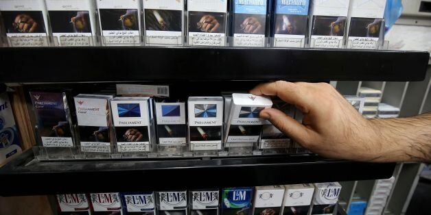 A picture taken on September 29, 2017 shows a close up shot of a vendor organizing cigarette boxes at...