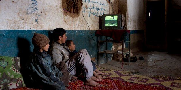 Children watch TV in their house in Tilmi village in the High Atlas region of Morocco February 13, 2015....