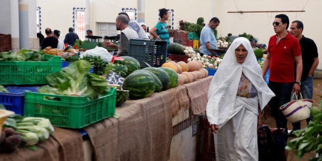 A women buys vegetables the first day of the holy fasting month of Ramadan at a market in Tunis, Tunisia,...