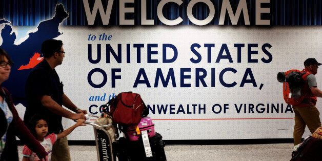 A family exits after clearing immigration and customs at Dulles International Airport in Dulles, Virginia,...