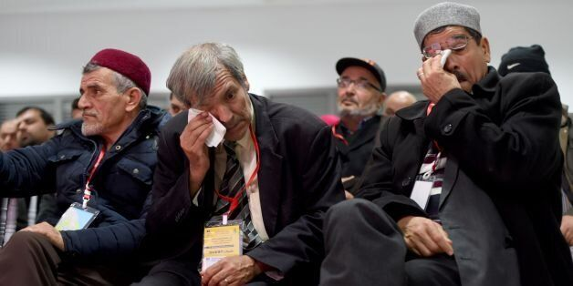 Men wipe their tears as relatives of abuse victims watch a live broadcast of testimonials by abuse victims...