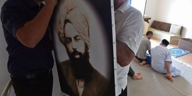 Members of Algeria's small Ahmadi community put up a photo of Mirza Ghulam Ahmad (1835-1908) the founder...
