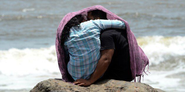 A young couple sit together on a rocky outcrop off the Arabian sea in Mumbai on July 3, 2015. AFP PHOTO...