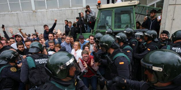 Scuffles break out between a crowd and Spanish Civil Guard officers, outside a polling station for the...