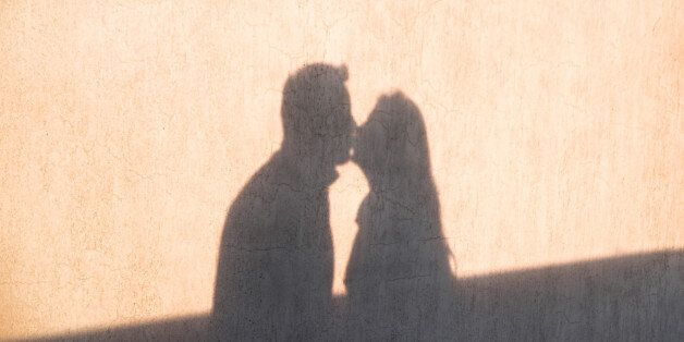 The shadow on the wall of a young loving couple kissing each other and enjoy the tenderness. Happy and...