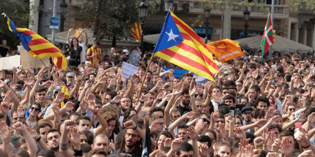 People shout as Esteladas (Catalan separatist flags) flutter during a protest the day after the banned...