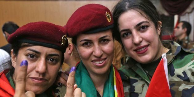Female members of a Kurdish Peshmerga battalion show their ink-stained fingers after casting their vote...