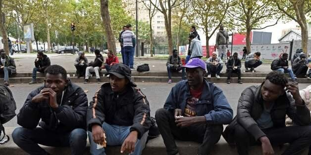 Migrants eat food distributed by the Utopia 56 association in a street of Paris on October 11, 2017.Unprecedented...
