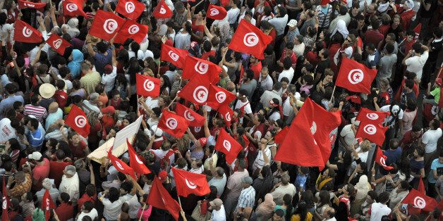 Tunisian demonstrators wave their national flag and shout slogans during a protest against the country's...