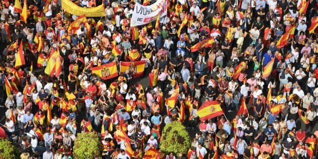 Protestors gather holding Spanish flags during a demonstration against independence of Catalonia called...