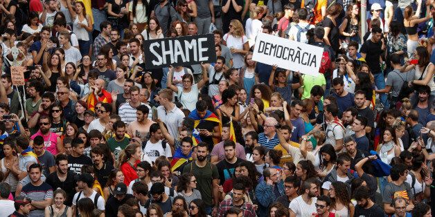 People hold up placards during a demonstration two days after the banned independence referendum in Barcelona,...